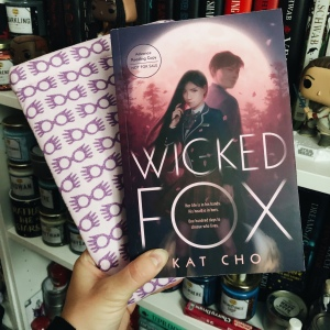 Wicked Fox book cover by author Kat Cho - shows two figures backlit as they are in front of a large moon and forest. Wicked Fox text is on top of this in the lower half of the image, with authors name also