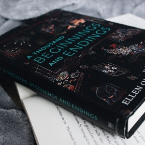 A Thousand Beginning and Endings by Ellen Oh and Elsie Chapman has a black cover with several small drawings on it including dragons. It is lay on an open book and surrounded by a grey blanket. The title of the book is position on the middle of the cover in teal writing.