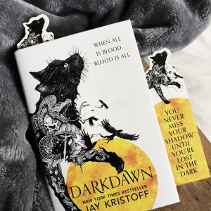 Darkdawn uk edition by Jay Kristoff. It has a white cover on it with a black cat walking onto the cover from the left side. The cat has lots of white stars inside it. There is a yellow semi circle coming from the bottom of the cover. The title and authors name are in black text against the yellow moon.
